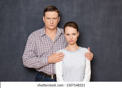 Studio half-length portrait of serious couple, dressed in casual clothes, man is putting his arms around woman's shoulders, both are looking strictly at camera, over gray background. Relations concept