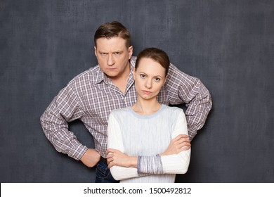 Studio half-length portrait of serious and dissatisfied caucasian man and woman wearing casual clothes, with frowning faces, looking with displeasure at camera, standing together over gray background