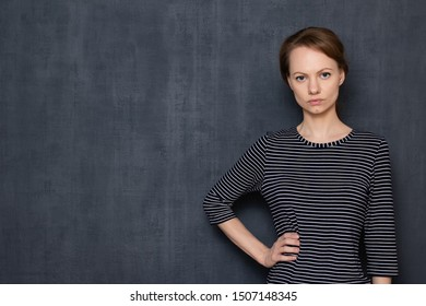 Studio half-length portrait of serious focused ambitious caucasian fair-haired girl wearing striped jumper, looking strictly at camera, holding arm on waist, over gray background, copy space on left