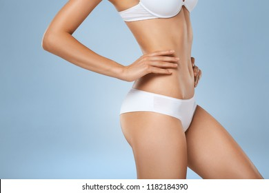 Studio HD capture of a unrecognizable young woman torso in underwear. Perfect slim tanned body - an example of sports, dieting, fitness or plastic surgery and aesthetic cosmetology