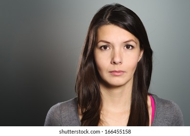 Studio head and shoulders portrait on grey of a beautiful serious young woman looking directly at the camera