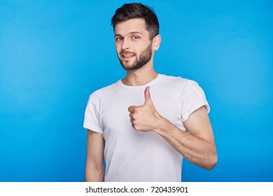 Studio headshot of happy young Caucasian man in white T-shirt, gesturing thumbs-up, telling you that you are doing a good job, looking and smiling at the camera with cheerful confident expression.