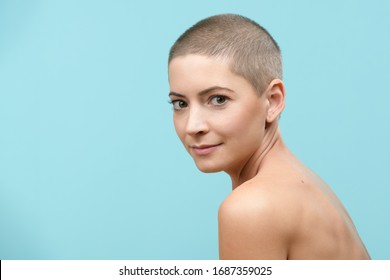 Studio headshot portrait of a beautiful young caucasian woman with shaved head against pastel blue background. Cancer survivor beauty portrait.