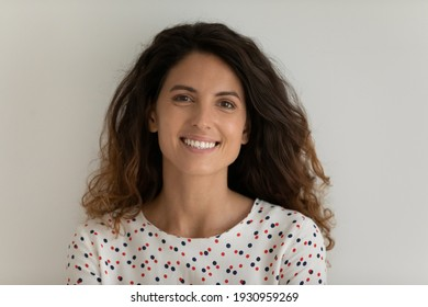 Studio headshot portrait of happy millennial woman with thick wavy hair flowed over shoulders. Pretty positive young female looking at camera demonstrate shiny smile. Isolated on light grey background