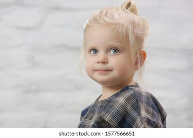 Studio headshot of two years old toddler girl looking at camera