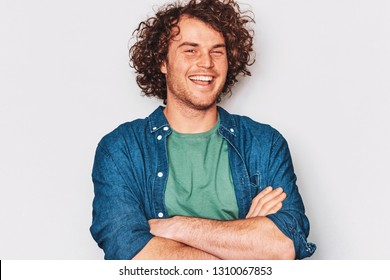 Studio horizontal image of smiling man posing for advertisement wears blue shirt, crossed his hands, isolated on white wall with copy space for your informational text. People and emotions