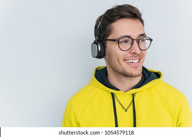 Studio horizontal portrait of happy smiling young male wearing yellow hoodie and round glasses, with headphones on head, listening favorite music, looking aside isolated on white background.Copy space
