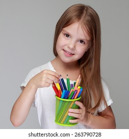 Studio image of a beautiful young caucasian girl in a white dress with colored pencils on a gray background