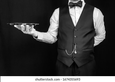 Studio Image of Butler or Waiter in Vest and White Gloves Holding Silver Tray. Concept of Service Industry and Professional Hospitality. Copy Space for Service and Courtesy