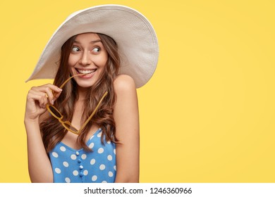 Studio image of dreamy woman with long wavy hair, looks with pleased expression, has intention to travel abroad, holds sunglasses in hand, wears summer hat, free space for slogan over yellow wall