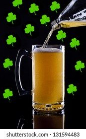 A studio image of a mug of beer with shamrocks in the background.