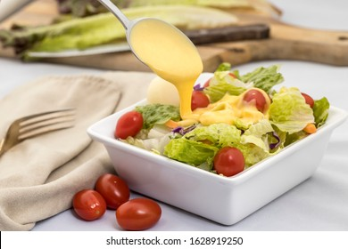 A studio image of a salad topped with cherry tomatoes and dressing being poured on it.