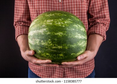 A studio image of an unidentified woman holding a large watermelon.