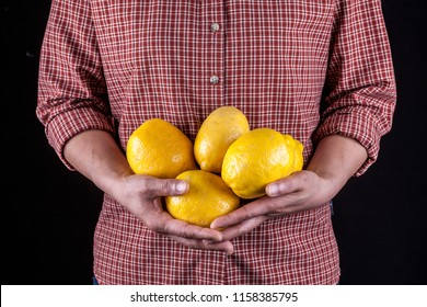 A studio image of an unidentified woman holding a bunch of lemons.