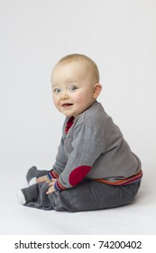 Studio Isolation of an Infant Child. The baby boy is Isolated on white with a vertical composition. He is very Cute and is sat smiling into the camera