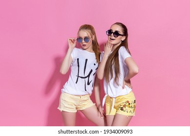 Studio lifestyle portrait of pretty two best friends sister girls, posing and having fun together at pink background, cool bloggers, bright clothes accessories and sunglasses, hugs, family relations.