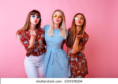 Studio lifestyle portrait of three happy positive women wearing trendy tropical outfits, and glasses, sending air kisses, group oh hipster best friend girls having fun, studio pink background.
