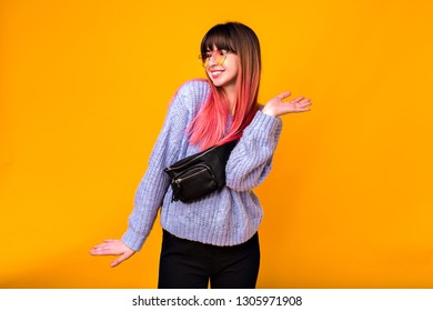 Studio lifestyle portrait of young happy woman, positive exited emotions, bright trendy fuchsia hairs, cozy sweater, pants and bum bag, yellow background.