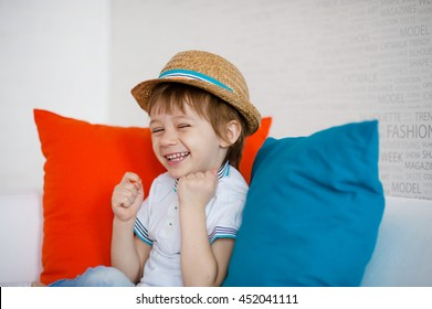 Studio. little boy in a straw hat and a white T-shirt shrugs and smiles