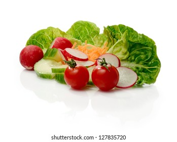 Studio macro of fresh green salad with radish, carrot and tomato against a white background. Copy space.