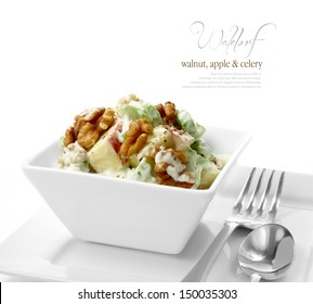 Studio macro of fresh Waldorf Salad with black pepper, walnuts, apple and celery against a white background. A perfect image for your restaurant showing attention to detail. Copy space.