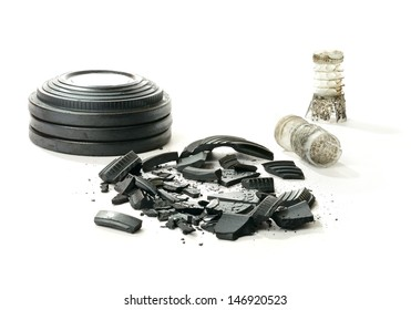 Studio macro of stacked clay pigeon targets a shattered clay and spent shotgun cartridges with soft shadows against a white background. Copy space.