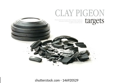 Studio macro of stacked clay pigeon targets and shattered clay with soft shadows against a white background. Copy space.