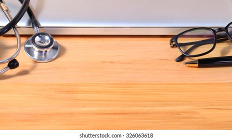 Studio macro of a stethoscope pen eyeglass and notebook with shallow DOF evenly matched abstract on wood table background
