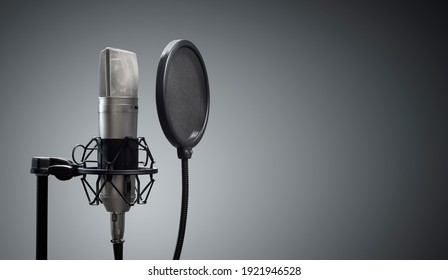 Studio microphone and pop shield on mic stand against gray background concept for podcast and presentation