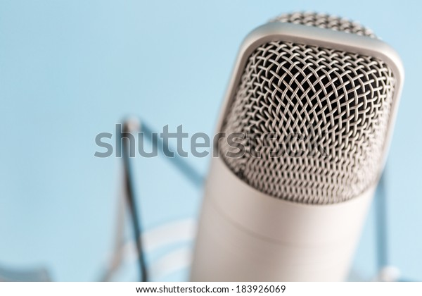 Studio microphone for recording podcasts on a blue background.