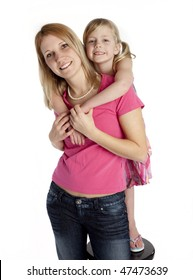 Studio photo of 6 year old girl embracing mother. White background.