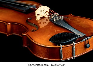 Studio photo of an aged violin shot against a black background.
