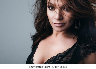 studio photo  of a beautiful sexy brunette Latina woman with makeup  on a gray background isolated. wind in hair. gold earrings