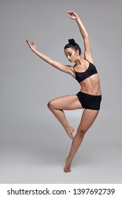 Studio photo of a beautiful woman ballerina dressed in black two-piece swimsuit doing a dance element on a gray background.