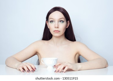 Studio photo brunette at the table.