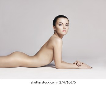 studio photo of elegant naked lady laying on white background