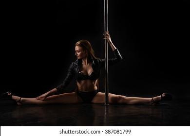 Studio photo of flexible pole dancer doing split