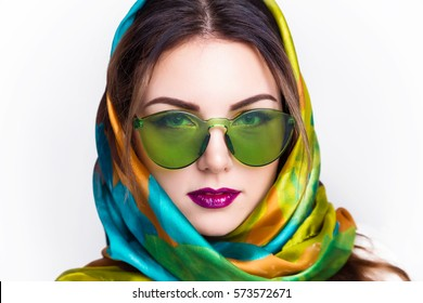 Studio photo of the girl in sunglasses and a scarf fun.Attractive young girl with dark hair and bordo lips wearing green trendy sunglasses, and scarf.