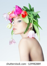 Studio photo of the girl with a wreath of tulips.