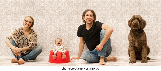 Studio photo of a happy family sitting next to each other