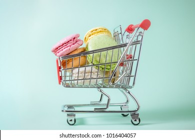 Studio photo of macarons in small metal shopping cart on green background. Minimal concept.