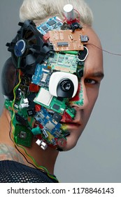 Studio photo of man cyborg, half face computer elements and with professional make-up, white Iroquois on head. Future technology concept