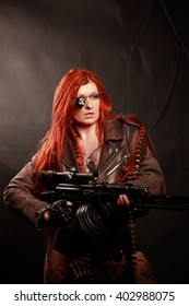 Studio photo shot of beautiful young redhead girl with lot of tattoo with studio requisite machine gun taken against the wall covered with dark fabric