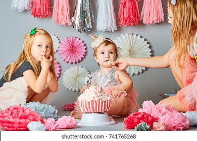 studio photo, three sisters on a gray background eat a cake