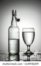 A studio photo of water in a glass next to a glass water bottle.