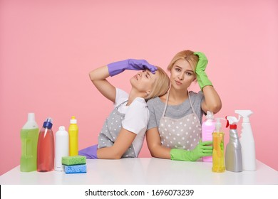 Studio photo of young blonde females dressed in basic t-shirts and aprons sitting over pink background with household chemicals, cleaning big house and being very tired