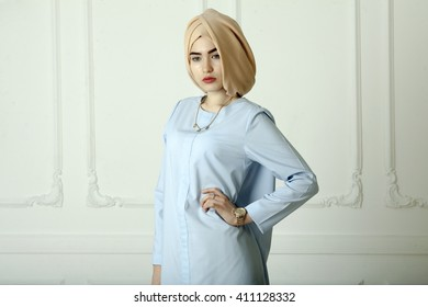 Studio photo of a young woman eastern type in the modern Muslim clothes and beautiful headdress