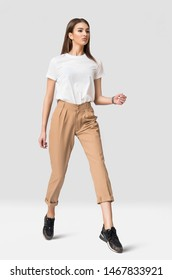 Studio photo of young woman model clothing in beige wool pants and whit t-shirt with monstera leaf in the hand. Clean photo of girl ideal for apparel mock-up design
