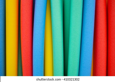 Studio photograph of a large group of floating swim noodles in different colors.