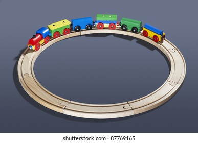 studio photography of a colorful wooden toy train on a track circle in dark back